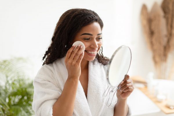 beautiful lady cleansing eyebrows with cotton wipes after appointment